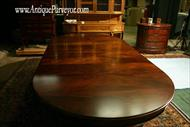 Large round mahogany dining table with extensions makes an 10 foot oval shape