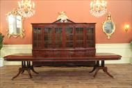 Mahogany dining table shown with birdcage pedestals in front of higher end china cabinet