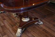 Mahogany dining table with gold leaf accented Regency style pedestals