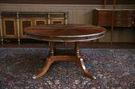 Expandable round dining table on antique style Duncan Phyfe birdcage pedestal.