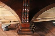 Foot details on a large round mahogany dining table.