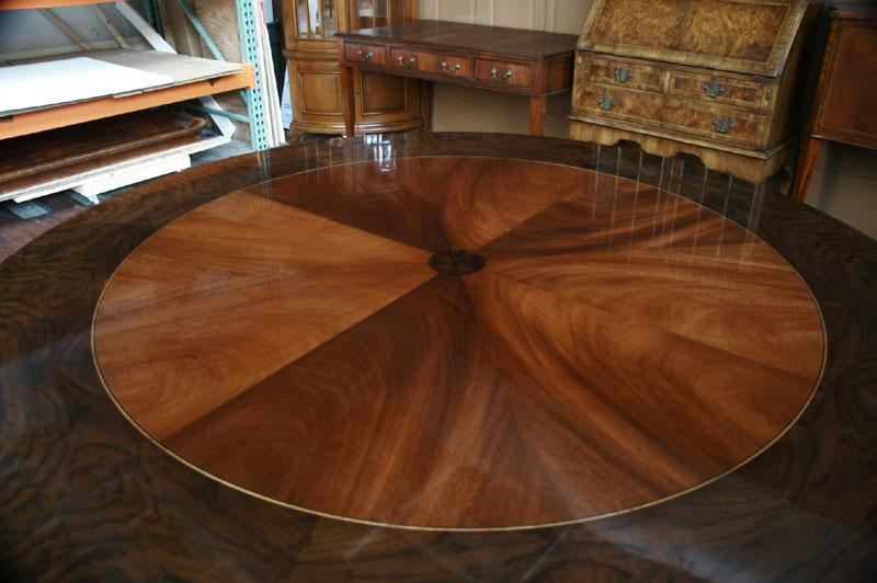 table top has a wide burly walnut border and a pie cut swirl mahogany