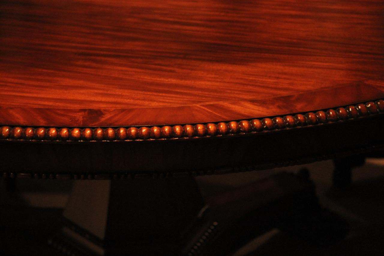 72 round mahogany table with beaded edging and carved pedestal base in the regency style